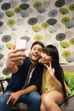 Jeunes couples heureux utilisant le smartphone dans la barre Images stock