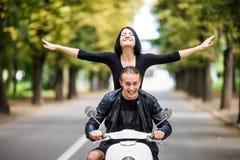 Jeunes couples heureux voyageant dans le scooter dans la vieille ville européenne La femme apprécient le voyage avec les mains ri Images libres de droits