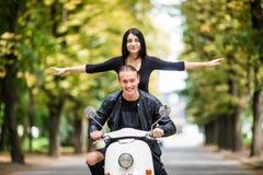 Jeunes couples heureux voyageant dans le scooter dans la vieille ville européenne La femme apprécient le voyage avec les mains ri Image libre de droits