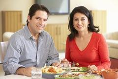 Jeunes couples hispaniques appréciant le repas à la maison Image libre de droits