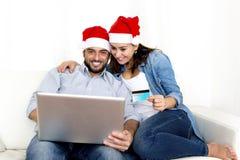 Jeunes couples hispaniques attrayants dans des achats en ligne de Noël d'amour avec l'ordinateur Photos stock