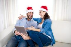 Jeunes couples hispaniques attrayants dans le comprimé numérique de achat de Noël en ligne d'amour Images libres de droits