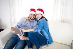 Jeunes couples hispaniques attrayants dans le comprimé numérique de achat de Noël en ligne d'amour Photo stock