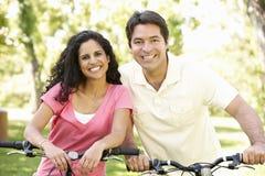 Jeunes couples hispaniques faisant un cycle en parc Images libres de droits