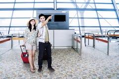 Jeunes couples indiquant l'information de vol Images stock