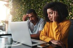 Jeunes couples inquiétés utilisant l'ordinateur portable en café image stock