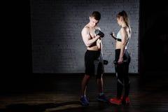 Jeunes couples intenses établissant avec des haltères bodybuilders Photographie stock