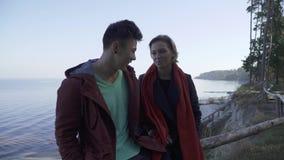 Jeunes couples interraciaux de sourire dans la tenue de détente se reposant par la falaise sur un fond des pins et d'un lac multi clips vidéos