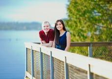 Jeunes couples interraciaux se tenant ensemble sur l'overlo en bois de pilier Images libres de droits