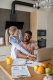 Jeunes couples interraciaux utilisant l'ordinateur portable prenant ensemble le petit déjeuner à la maison photographie stock
