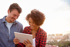 Jeunes couples intimes riant avec un comprimé Image libre de droits