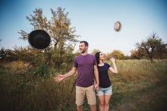 Jeunes couples jetant des chapeaux en l'air dans l'air Images stock