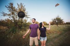 Jeunes couples jetant des chapeaux en l'air dans l'air Photo stock