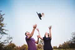 Jeunes couples jetant des chapeaux en l'air dans l'air Photographie stock libre de droits
