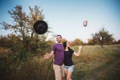 Jeunes couples jetant des chapeaux en l'air dans l'air Photo libre de droits