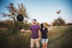 Jeunes couples jetant des chapeaux en l'air dans l'air Image libre de droits