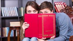 Jeunes couples jetant un coup d'oeil au-dessus d'un livre rouge Photo libre de droits