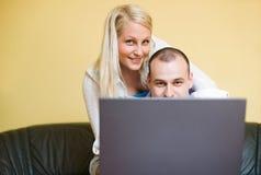 Jeunes couples jetant un coup d'oeil au-dessus de l'écran d'ordinateur portatif Photo libre de droits