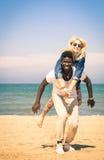 Jeunes couples jouant à la plage - amusement avec le saut de ferroutage Photos stock