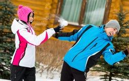 Jeunes couples jouant aux boules de neige et ayant l'amusement Photos stock
