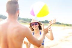 Jeunes couples jouant avec une boule à la plage Photos stock