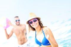 Jeunes couples jouant avec une boule à la plage Images stock