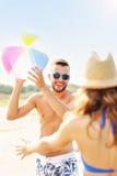 Jeunes couples jouant avec une boule à la plage Photo stock