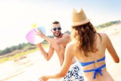 Jeunes couples jouant avec une boule à la plage Photo libre de droits