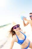 Jeunes couples jouant avec une boule à la plage Image stock
