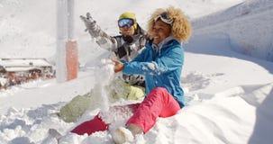 Jeunes couples jouant dans la neige à une station de sports d'hiver Images stock