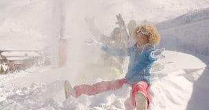 Jeunes couples jouant dans la neige à une station de sports d'hiver Photo libre de droits