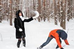 Jeunes couples jouant dans la neige, ayant le combat de boule de neige Photos stock