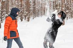 Jeunes couples jouant dans la neige, ayant le combat de boule de neige Photos libres de droits