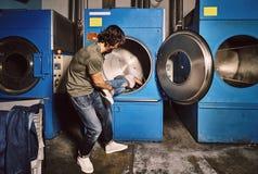 Jeunes couples jouant dans une blanchisserie industrielle images libres de droits
