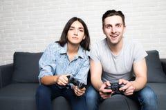 Jeunes couples jouant des jeux vidéo avec l'amusement à la maison Photos libres de droits