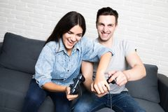 Jeunes couples jouant des jeux vidéo avec l'amusement à la maison Photos stock