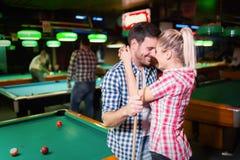 Jeunes couples jouant ensemble la piscine dans la barre Images stock