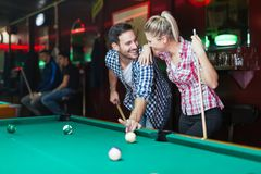 Jeunes couples jouant ensemble la piscine dans la barre Photo stock