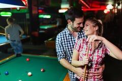 Jeunes couples jouant ensemble la piscine dans la barre Photo libre de droits