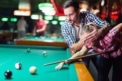 Jeunes couples jouant ensemble la piscine dans la barre Images libres de droits