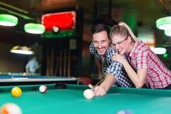Jeunes couples jouant ensemble la piscine dans la barre Photographie stock libre de droits