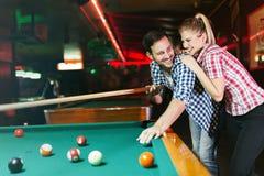Jeunes couples jouant ensemble la piscine dans la barre Image stock
