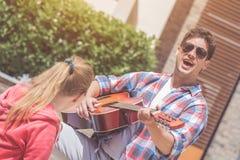 Jeunes couples jouant la guitare acoustique et chantant leur favori Photographie stock