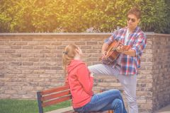 Jeunes couples jouant la guitare acoustique et chantant leur favori Photo stock