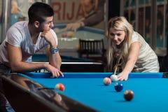 Jeunes couples jouant la piscine ensemble Photographie stock