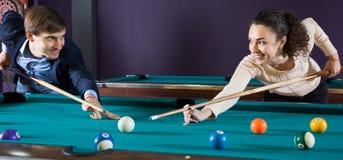 Jeunes couples jouant la piscine regardant l'un l'autre Images libres de droits