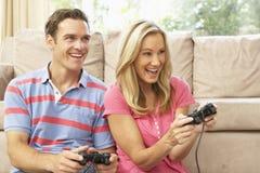 Jeunes couples jouant le jeu d'ordinateur sur le sofa à la maison photo stock