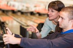 Jeunes couples jouant le simulateur de course au bowling Images libres de droits