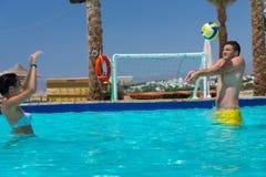 Jeunes couples jouant le volleyball dans la piscine Image stock