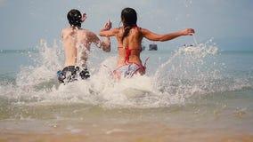 Jeunes couples joyeux fonctionnant dans la mer tropicale appréciant le temps de vacances dans le mouvement lent 1920x1080 banque de vidéos